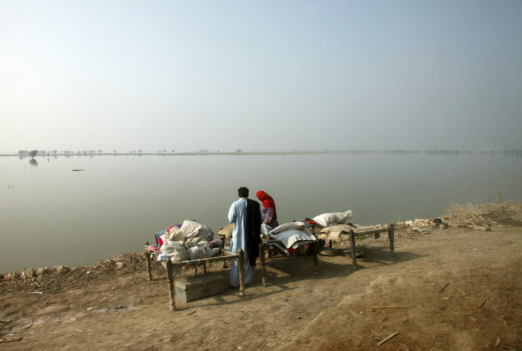Families returning to their communities following the flooding in Pakistan are often being forced to camp by the roadside, as the flood waters have still not receded sufficiently for them to return to their homes. This family are setting up 'charpoy' beds next to a vast expanse of water. The UK government is working with the government of Pakistan, other donor governments, international NGOs and UN agencies to meet the immediate humanitarian needs of more than 20 million people who were affected by the floods, such as shelter, water, sanitation and basic healthcare.